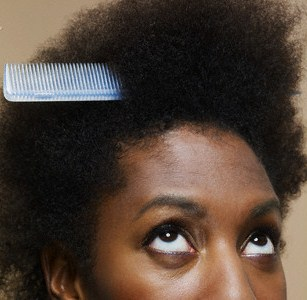Woman looking up at comb in her hair